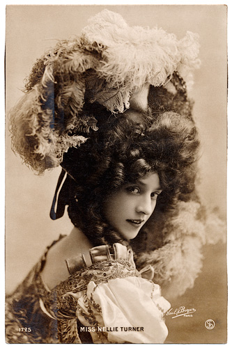Image of actress with large ruffled hat. She is turning to look at us over her right shoulder. The photo is in sepia.